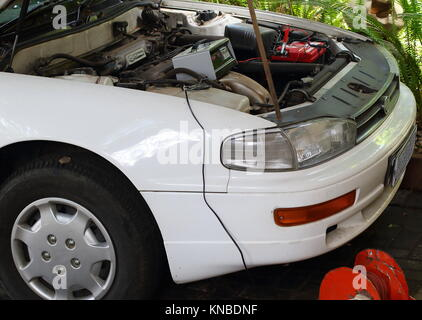 Charging the flat battery of an automobile using a freestanding battery charger image in landscape format - Stock Photo