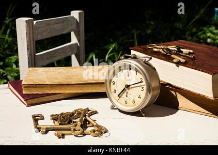 Vintage still life with old alarm clock, keys and books on a white wooden table. - Stock Photo