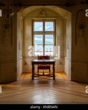 A solitaire chair and table in an ampty room of a castle - Stock Photo