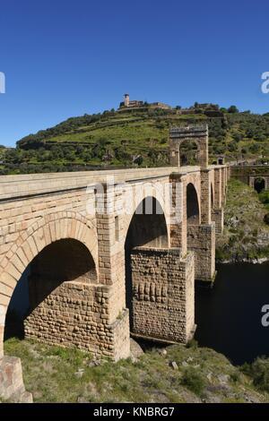 Roman bridge over the Tajo river in Alcantara, Extremadura, Spain. (In the top view of the town of Alcantara). - Stock Photo