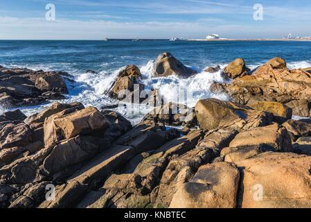 Rocks on the beach in Nevogilde civil parish of Porto, Portugal. Port of Leixoes Cruise Terminal building on background. - Stock Photo
