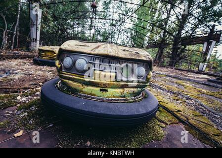 Bumper cars in amusement park of Pripyat ghost city, Chernobyl Nuclear Power Plant Zone of Alienation in Ukraine. - Stock Photo