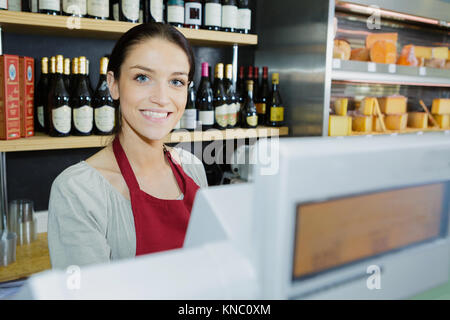 beautiful female food store employee at the cashier smiling - Stock Photo
