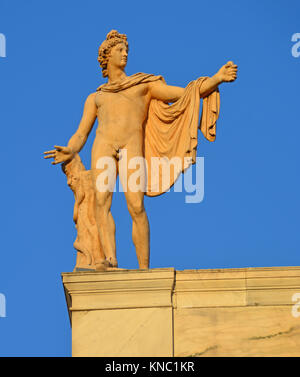 Greek God of the Sun Apollo also god of music, truth and prophesy, with python on a tree trunk. Ancient greek statue - Stock Photo