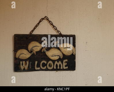 A dilapidated and weathered wooden welcome sign with a letter missing hanging on a dirty and cracked wall image - Stock Photo