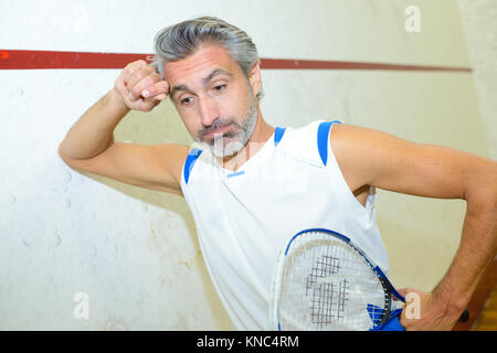 squash player looking exhausted - Stock Photo