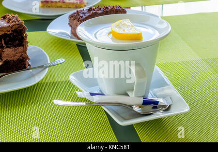 White porcelain cup of tea with lemon, sugar, spoon on a table in the cafeteria. - Stock Photo