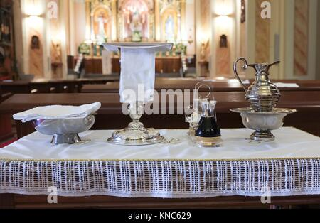 Catholic liturgical objects displayed over table at church. Chalice, communion wafers, wine, water, ewer and basin. - Stock Photo