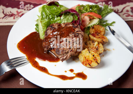 Grilled sirloin beef steak with potato wedges and green salad served in a local warung (small family owned restaurant). - Stock Photo