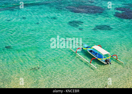 Indonesian outrigger canoe, also known as jukung or cadik moored in Mendira Bay. Candidasa, Manggis subdistrict, - Stock Photo
