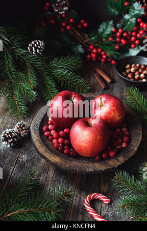 Red apples, cranberries and fir tree branches. Christmas still life. Winter wallpaper. Vertical composition - Stock Photo