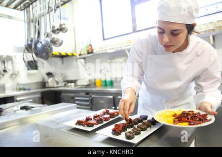 Chef plating blood sausage with red pepper, Cook in cooking school, Cuisine School, Donostia, San Sebastian, Gipuzkoa, - Stock Photo