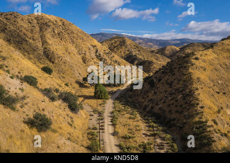 Narrow gravel trail leads between high hills in the desert of southern California's wilderness. - Stock Photo