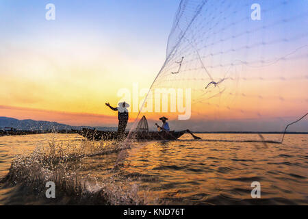 Silhouette of fishermen using nets to catch fish at the Bangpra lake with beautiful scenery of nature during sunrise - Stock Photo