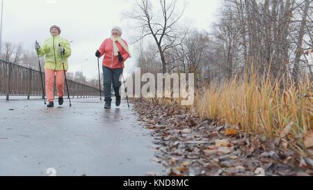 Two elderly grandma female doing exercises in the park - Stock Photo