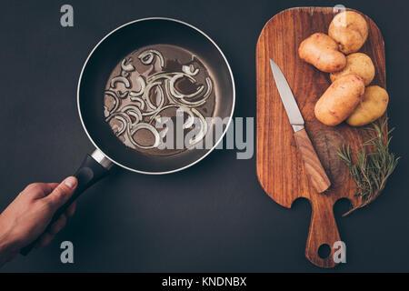 man putting frying pan - Stock Photo