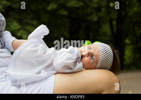 Little girl in white dress, socks and knitted headband lies on her mother's lap - Stock Photo