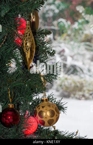 christmas tree decorations snow in garden baubles lights - Stock Photo