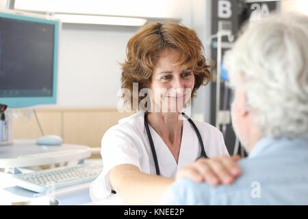 Patient in hospital room attended by a doctor, Hospital - Stock Photo