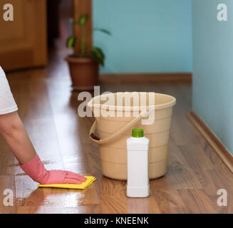 Close up of famale hands holding a washcloth and washing flooring. The man is kneeing. He is wearing yellow gloves - Stock Photo