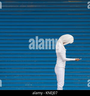 Woman in a white wig standing in front of a blue wall looking at her mobile phone