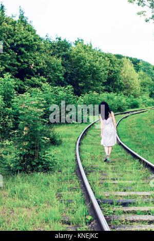 Girl walking on railway near forest. Walks to wonderland, pastel colors - Stock Photo
