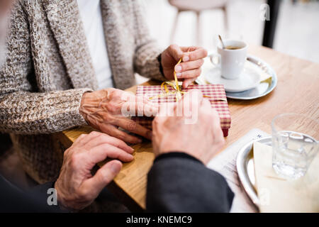 Senior couple with a present in a cafe. Christmas time. - Stock Photo
