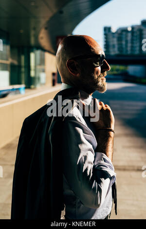 Portrait of mature businessman standing outdoors, carrying suit jacket over shoulder, side view - Stock Photo