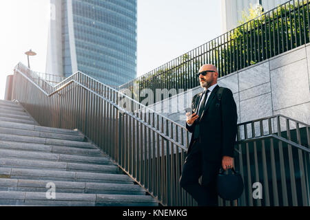 Mature businessman standing on steps, using smartphone, low angle view - Stock Photo