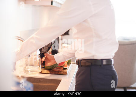 Mid section of man filling coffee percolator in kitchen - Stock Photo