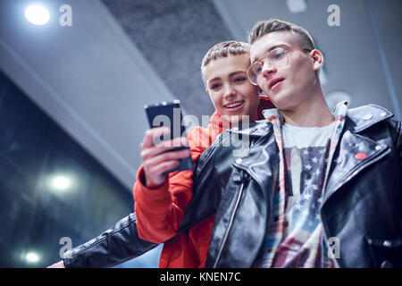 Young couple moving down underground station escalator  looking at smartphone - Stock Photo