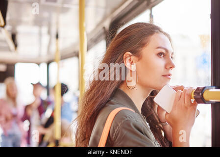 Young woman on city tram gazing out through window - Stock Photo