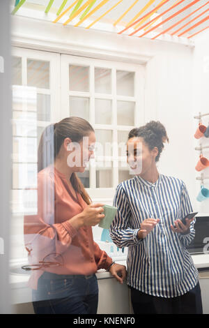 Two businesswomen laughing while taking a coffee break in office kitchen - Stock Photo