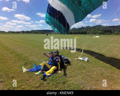 Portrait of tandem skydivers giving thumbs up after field landing - Stock Photo