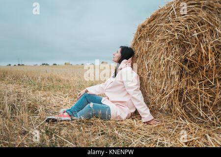 Woman in raincoat by hay bale, Odessa, Ukraine - Stock Photo