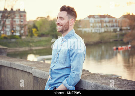Bearded young man leaning against bridge over River Thames, Richmond, UK - Stock Photo
