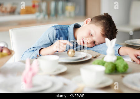 Boy at dining table playing with golden easter egg on plate - Stock Photo