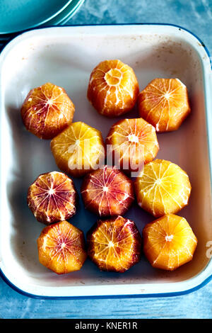 Peeled blood oranges in baking tray, elevated view - Stock Photo