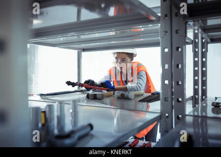 Female apprentice selecting tools at railway engineering facility - Stock Photo