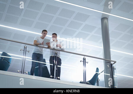 Apprentices working together using digital tablet in railway engineering facility - Stock Photo