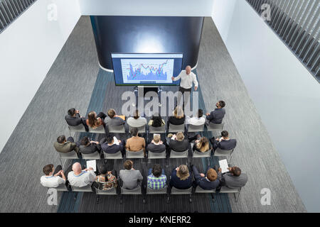 Instructor giving lecture to audience in railway engineering facility - Stock Photo