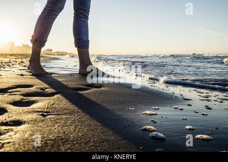 Legs of barefooted woman standing at water's edge on beach, Riccione, Emilia-Romagna, Italy - Stock Photo