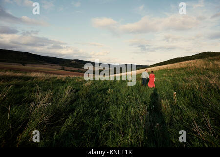 Rear view of mid adult couple holding hands while strolling in fields - Stock Photo
