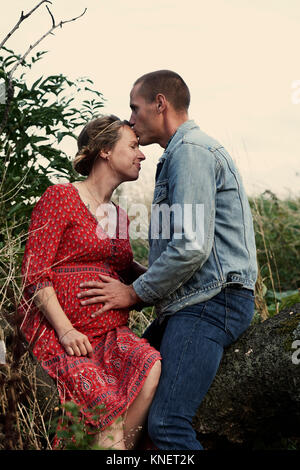 Romantic man kissing pregnant wife's forehead on tree trunk - Stock Photo