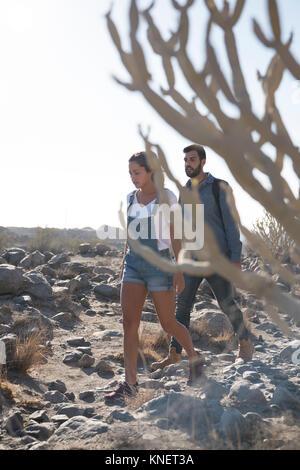 Young hiking couple hiking over rocks, Las Palmas, Canary Islands, Spain - Stock Photo