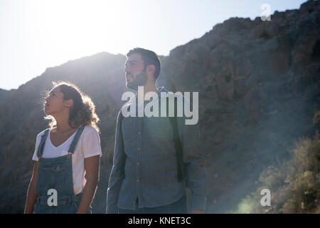 Young hiking couple looking up from sunlit valley, Las Palmas, Canary Islands, Spain - Stock Photo
