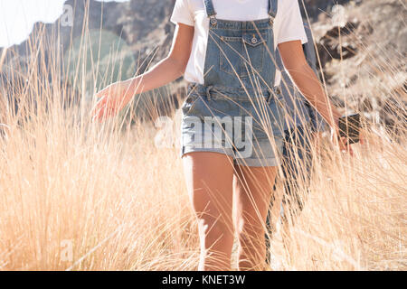 Mid section of young hiking couple touching long grass while hiking in valley, Las Palmas, Canary Islands, Spain - Stock Photo