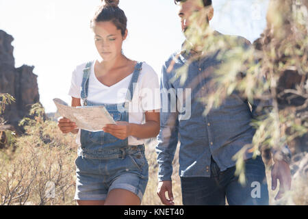 Young hiking couple looking at map in valley, Las Palmas, Canary Islands, Spain - Stock Photo