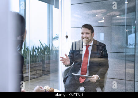 View through glass wall of colleagues having meeting in office - Stock Photo