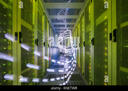 Interior of data centre, lights trails showing travelling data - Stock Photo